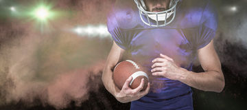 Imagem composta do capacete vestindo do jogador dos esportes ao guardar a bola Foto de Stock