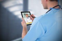 Imagem composta do cirurgião que usa a tabuleta digital Fotografia de Stock