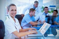 Imagem composta do doutor de sorriso bonito que datilografa no teclado com sua equipe atrás foto de stock royalty free