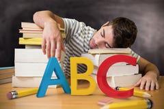 Imagem composta do estudante adormecida na biblioteca Foto de Stock