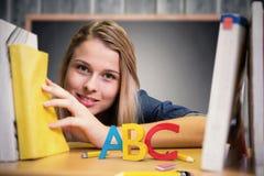 Imagem composta do estudante bonito na biblioteca Fotos de Stock