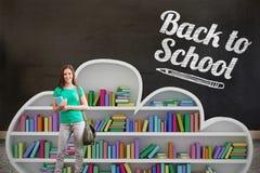 Imagem composta do estudante que sorri na câmera na biblioteca imagem de stock royalty free