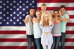Imagem composta do grupo de adolescentes que estão na frente da câmera com polegares acima fotografia de stock