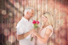 Imagem composta do homem afetuoso que oferece suas rosas do sócio Foto de Stock