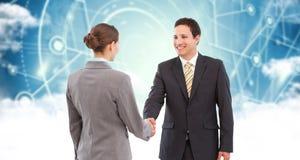 Imagem composta do homem de negócios de sorriso que agita as mãos com colega Imagem de Stock Royalty Free