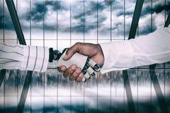 Imagem composta do homem de negócios e do robô que agitam as mãos Foto de Stock