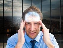 Imagem composta do homem de negócios novo com dor de cabeça severa foto de stock royalty free
