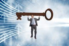 Imagem composta do homem de negócios que leva a grande chave com os braços aumentados Fotografia de Stock