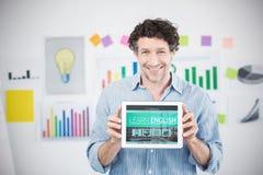 Imagem composta do homem de negócios que mostra a tabuleta 3d digital com a tela vazia no escritório criativo Foto de Stock