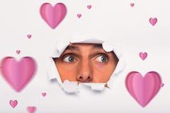 Imagem composta do homem novo que olha através do rasgo de papel Fotografia de Stock Royalty Free