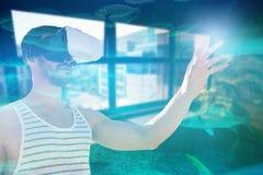 Imagem composta do homem novo que usa vidros da realidade virtual Imagens de Stock