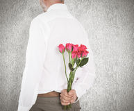 Imagem composta do homem que guarda o ramalhete das rosas atrás para trás Imagens de Stock Royalty Free