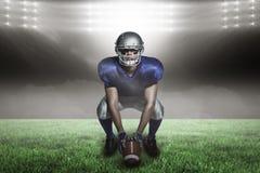 Imagem composta do jogador de futebol americano com bola que agacha-se com 3d Imagens de Stock