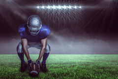 Imagem composta do jogador de futebol americano na bola guardando uniforme ao agachar-se Fotos de Stock