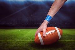 Imagem composta do jogador de futebol americano que coloca a bola 3D Foto de Stock