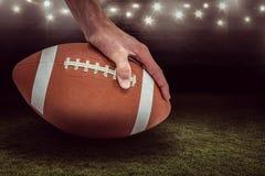 Imagem composta do jogador de futebol americano que coloca a bola 3D Imagens de Stock