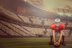 Imagem composta do jogador de futebol americano que dobra-se ao guardar a bola com 3d Fotos de Stock Royalty Free