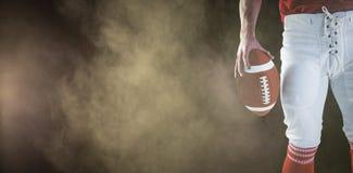 Imagem composta do jogador de futebol americano que sustenta o futebol Foto de Stock