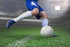 Imagem composta do jogador de futebol que retrocede a bola foto de stock royalty free