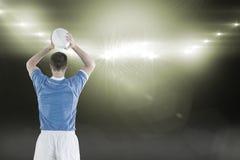 Imagem composta do jogador do rugby aproximadamente para jogar uma bola de rugby 3D imagem de stock