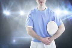 Imagem composta do jogador do rugby que entrega uma bola de rugby imagem de stock