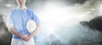 Imagem composta do jogador do rugby que entrega uma bola de rugby fotos de stock