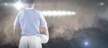 Imagem composta do jogador do rugby que guarda uma bola de rugby foto de stock