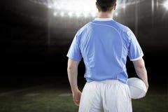 Imagem composta do jogador do rugby que guarda uma bola de rugby fotografia de stock royalty free