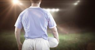 Imagem composta do jogador do rugby que guarda uma bola de rugby fotografia de stock