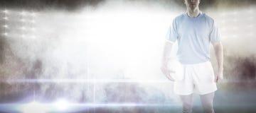 Imagem composta do jogador do rugby que guarda uma bola de rugby fotos de stock royalty free