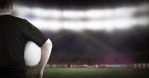 Imagem composta do jogador do rugby que guarda uma bola de rugby imagens de stock