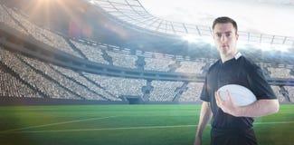 Imagem composta do jogador do rugby que guarda uma bola de rugby 3D imagens de stock