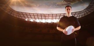 Imagem composta do jogador do rugby que guarda uma bola de rugby 3D fotos de stock royalty free