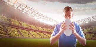 Imagem composta do jogador do rugby que joga uma bola de rugby 3D Fotografia de Stock Royalty Free