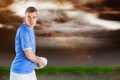 Imagem composta do jogador do rugby que joga uma bola de rugby 3D Fotografia de Stock