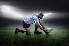 Imagem composta do jogador do rugby que mantém a bola em retroceder o T fotos de stock