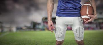 Imagem composta do jogador dos esportes que guarda a bola Imagens de Stock Royalty Free