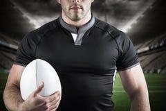 Imagem composta do jogador resistente do rugby que guarda a bola Fotos de Stock