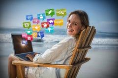 Imagem composta do louro lindo que senta-se na cadeira de plataforma usando o portátil na praia 3d Imagem de Stock Royalty Free