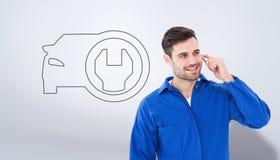 Imagem composta do mecânico masculino novo feliz que usa o telefone celular Foto de Stock Royalty Free