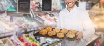 Imagem composta do padeiro que mostra o pão contra o fundo branco Foto de Stock