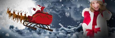 Imagem composta do presente guardando louro festivo e de apontar do Natal seu dedo imagem de stock