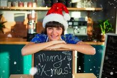 Imagem composta do retrato da empregada de mesa de sorriso que veste o chapéu de Santa e que senta-se com placa do sinal x-mas Imagens de Stock Royalty Free