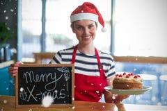 Imagem composta do retrato da empregada de mesa que guarda a ardósia com sinal x-mas e o bolo alegres imagens de stock