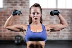 Imagem composta do retrato da mulher com as luvas que dobram os músculos imagens de stock
