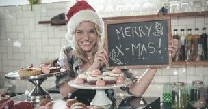 Imagem composta do retrato da mulher que guarda o quadro-negro com Feliz Natal imagens de stock