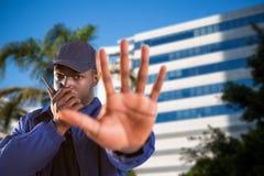 Imagem composta do retrato da segurança segura que fala no Walkietalkie e que faz o gesto da parada Fotografia de Stock