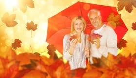 Imagem composta do retrato de pares felizes sob o guarda-chuva vermelho fotos de stock royalty free