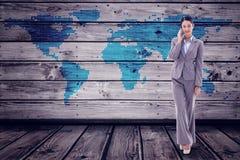 Imagem composta do retrato de uma mulher de negócios nova que faz um telefonema imagem de stock