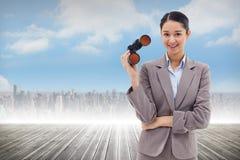 Imagem composta do retrato de uma mulher de negócios que guarda binóculos fotos de stock